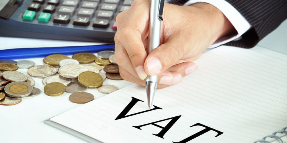 Hand with pen pointing to VAT (or Value Added Tax) sign on the paper - commercial & taxation concept