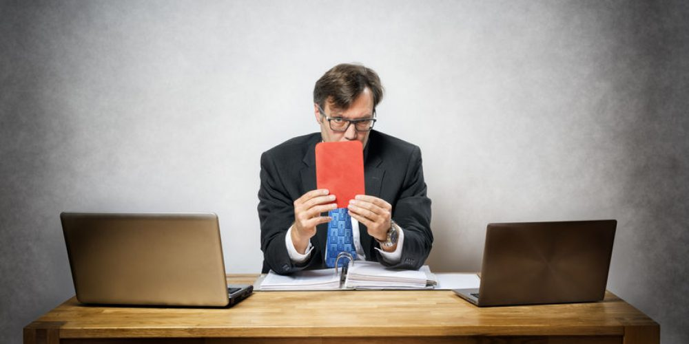 Image of business man with red card in office