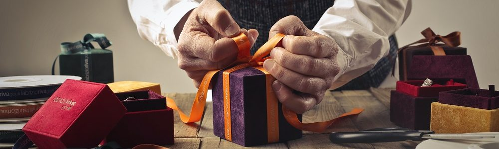 person-tying-ribbon-on-purple-gift-box-1050256